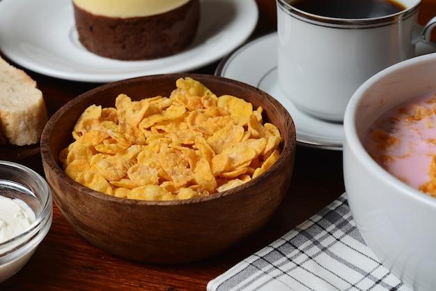Primo piano di torta di frutto della passione, pane tostato, caffè, yogurt, cereali.