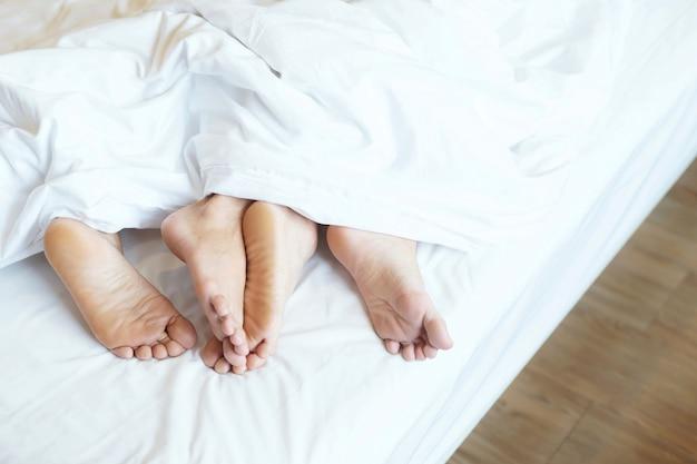 Chiuda in su della giovane coppia asiatica appassionata che fa sesso sul letto