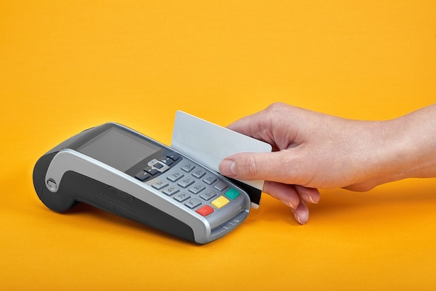 Primo piano dei pulsanti della macchina di pagamento con la mano umana che tiene la carta di plastica nelle vicinanze su sfondo giallo