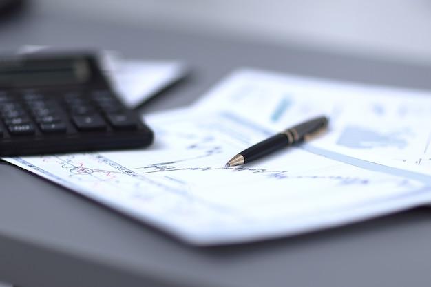 Close up.pen, grafico finanziario e calcolatrice sulla scrivania dell'uomo d'affari
