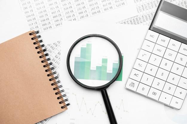 Chiuda in su della penna sul blocco note, calcolatrice di documenti aziendali con lente di ingrandimento in background