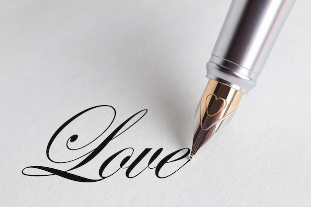 Primo piano di una penna che scrive la parola amore.