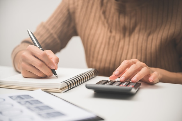 Chiuda in su della mano della gente lavora con la calcolatrice per affari e finanza.