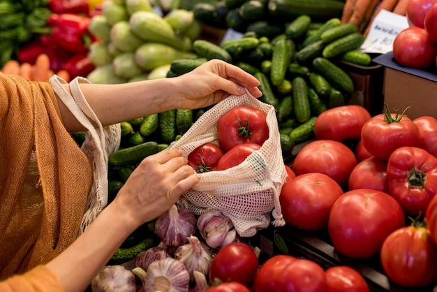 Persona del primo piano che compra i pomodori