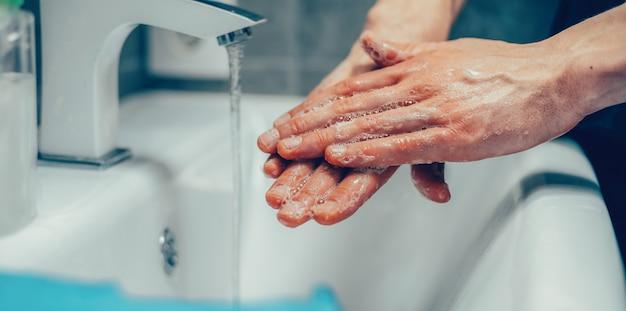 Avvicinamento. persona che si insapona accuratamente i palmi delle mani