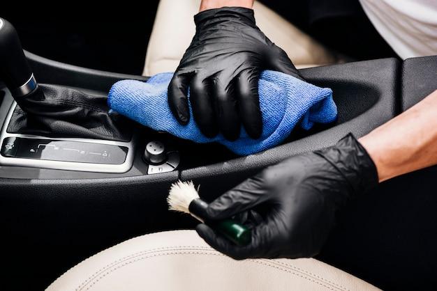 Chiuda in su della persona che pulisce l'interno dell'automobile Foto Premium
