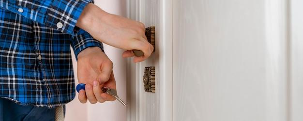 Una persona da vicino torna a casa e apre la porta con le chiavi wide webn banner