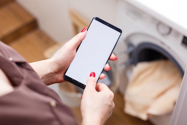 Close-up di persona che opera a mano smart lavatrice utilizzando il telefono cellulare app