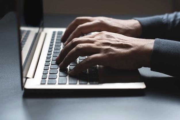 Primo piano della mano della persona che digita sulla tastiera del laptop, autore che utilizza internet sul computer notebook, vista laterale