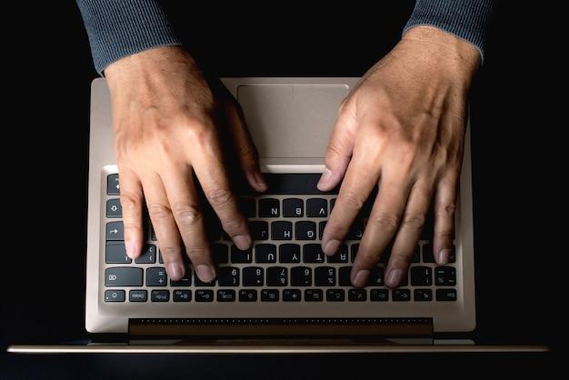 Primo piano della mano della persona che digita sulla tastiera del laptop, autore che utilizza internet sul computer notebook, vista dall'alto