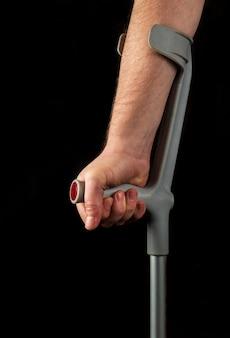 Primo piano della mano della persona con le stampelle dell'avambraccio. immagine verticale di sfondo nero isolato. vista laterale