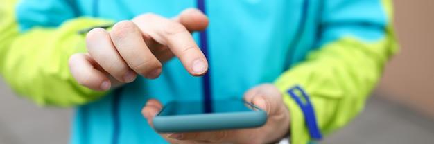 Primo piano della stampa della persona con il dito sullo schermo dello smartphone. uomo sms o navigare su internet. umani che indossano abbigliamento sportivo all'aperto. concetto di tecnologia e intrattenimento
