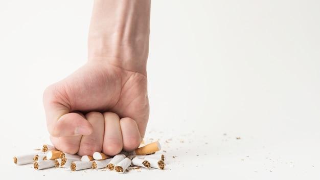 Primo piano della mano di una persona che rompe le sigarette con il suo pugno su sfondo bianco