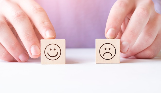 Primo piano della mano della persona che tiene il blocco di legno con la faccia felice e infelice sulla scrivania riflettente