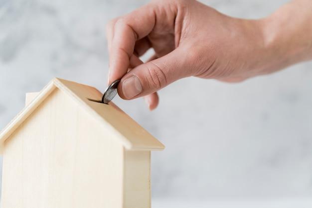 Primo piano della mano della persona che inserisce la moneta nel porcellino salvadanaio di legno della casa