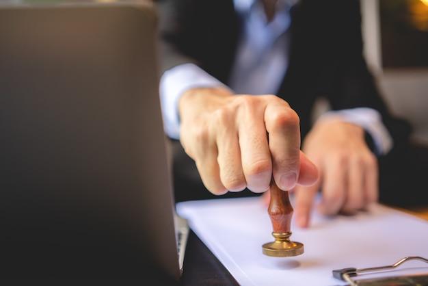 Primo piano della timbratura a mano di una persona con timbro approvato sul documento del certificato di approvazione documento pubblico alla scrivania, notaio o uomini d'affari lavorano da casa, isolati per la protezione da coronavirus covid-19