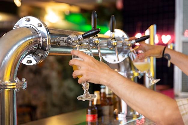 Chiuda in su delle mani della persona che riempiono due boccali di birra contemporaneamente in un bar. messa a fuoco selettiva.