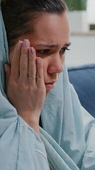 Primo piano di una persona con l'influenza che guarda il termometro