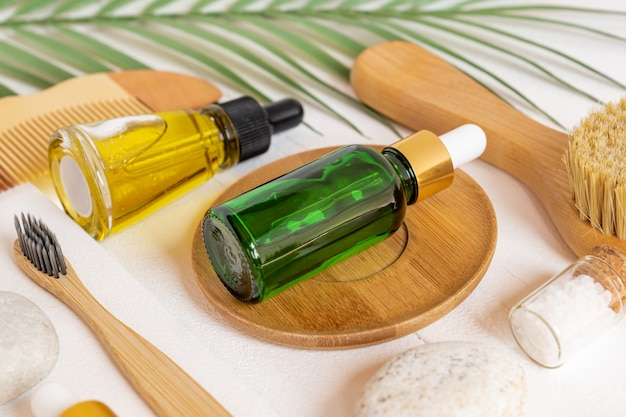 Primo piano di accessori personali e cosmetici per la cura del viso. oli organici naturali per trattamenti di bellezza, spazzole per viso e denti e pettine di legno con foglie verdi su tavolo bianco