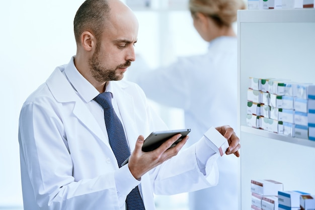 Avvicinamento. farmacista con una tavoletta digitale guardando una scatola di medicinali.