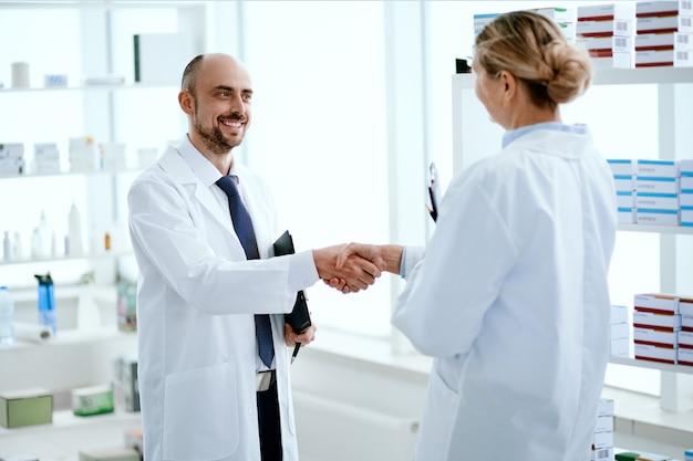 Avvicinamento. il personale della farmacia si saluta con una stretta di mano.