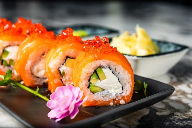 Un primo piano di philadelphia involtini di sushi con salmone affumicato, crema di formaggio e avocado su una piastra nera