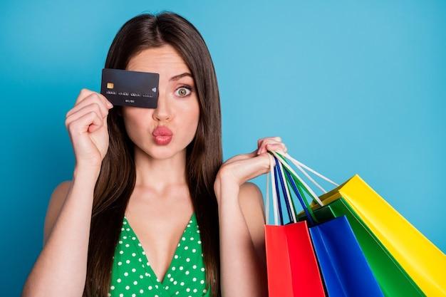 Foto ravvicinata della ragazza stupita chiudere la copertura dell'occhio della carta di credito rende le labbra carnose imbronciate tenere molte borse indossare canottiera verde punteggiata ritagliata canotta isolata su sfondo di colore blu
