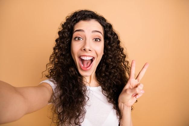 Close up foto di incredibile signora che fa selfie trentadue denti sorridente che mostra v-segno simbolo allegro indossare abiti casual bianchi isolato beige pastello colore di sfondo