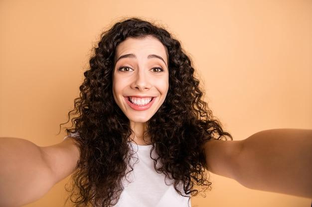 Close up foto di incredibile signora che fa selfie toothy sorridente libero professionista della rete sociale indossare abiti casual bianchi isolati beige pastello colore di sfondo