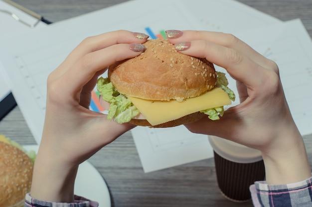 Foto ravvicinata di un hamburger appetitoso nelle mani di un giovane lavoratore contro il posto di lavoro