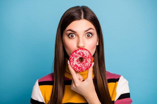 Close up foto di stupita ragazza pazza nasconde le labbra con ciambella ascolta incredibili informazioni sulla dieta urlare wow omg indossare un bell'aspetto abbigliamento isolato sopra la parete di colore blu