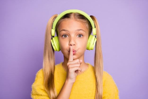 Close up foto di bambino stupito utilizzare auricolare ascoltare musica trovare melodia nella playlist mostra il dito indice non dire informazioni riservate indossare pullover isolato parete di colore viola