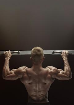 Foto del primo piano del tipo muscolare attraente del culturista che fa retrovisione di tirata
