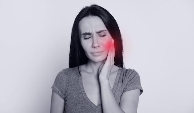 Foto ravvicinata di una ragazza attraente e triste, che guarda nell'angolo in alto a destra, tenendole la guancia con il braccio destro, come se avesse mal di denti