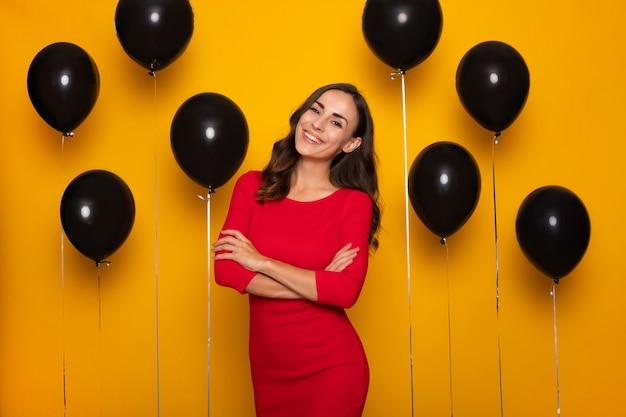 Foto ravvicinata di una donna castana sorridente e sicura di sé in abito rosso su sfondo nero di palloncini di elio nel giorno delle vendite