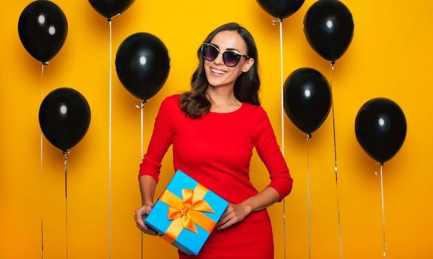 Foto ravvicinata di un'attraente donna bruna sorridente sicura di sé in abito rosso e occhiali con confezione regalo in mano su sfondo nero di palloncini di elio nel giorno delle vendite