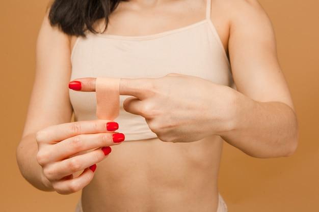 Foto ravvicinata di una giovane donna attraente in biancheria intima che incolla un cerotto antibatterico sul dito su sfondo beige.