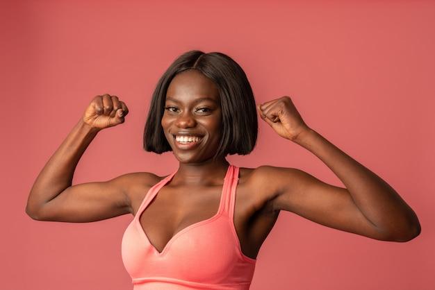 Chiuda sulla foto di bella femmina afroamericana in reggiseno rosa che mostra il suo bicipite