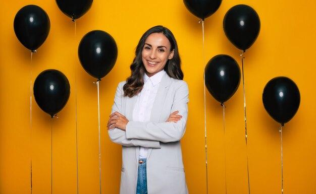 Foto ravvicinata di una bella donna d'affari bruna fiduciosa in abbigliamento casual intelligente su sfondo nero di palloncini di elio nel giorno delle vendite