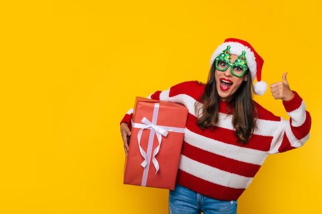 La foto ravvicinata di una bella donna sorridente eccitata con una scatola regalo di natale in mano mostra il pollice in su mentre posa su sfondo giallo