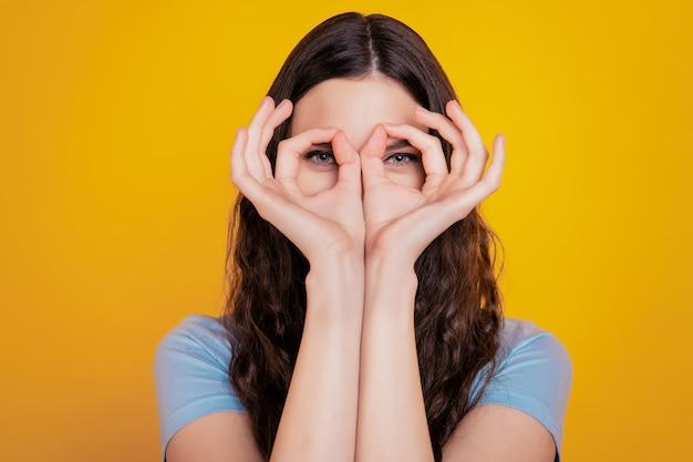 Primo piano foto bella ragazza mani dita alzate simbolo okey vicino agli occhi che ingannano sfondo giallo isolato