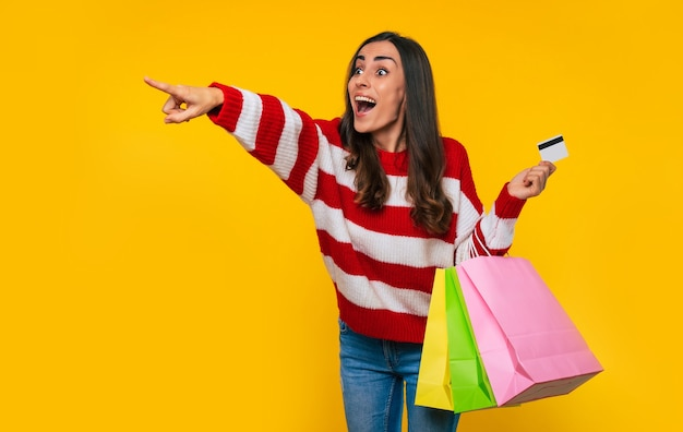 Foto ravvicinata di bella giovane donna felice ed eccitata in un maglione a righe con molte borse della spesa colorate e carta di credito nelle mani isolate su sfondo giallo