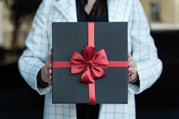 Foto ravvicinata della scatola nera con fiocco rosso in mani femminili. ragazza con una bella confezione regalo nelle sue mani.