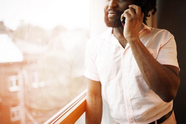 Chiuda sulla foto di un uomo di colore in camicia convenzionale che parla sul suo telefono vicino alla finestra
