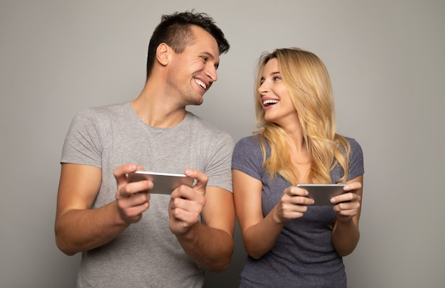 Foto ravvicinata di una ragazza bionda e del suo bel ragazzo, che stanno giocando ai giochi mobili sui loro smartphone con espressioni facciali concentrate.