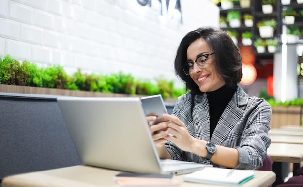 Foto ravvicinata di una donna d'affari in abito intelligente che scrive un messaggio su uno smartphone e sorride.