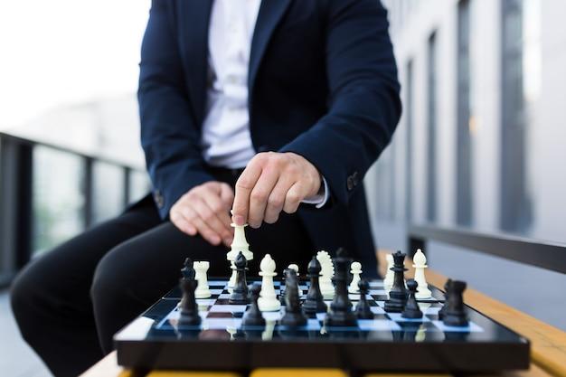 Foto ravvicinata delle mani dell'uomo d'affari che fanno una mossa su una scacchiera, uomo d'affari maschio che gioca a scacchi