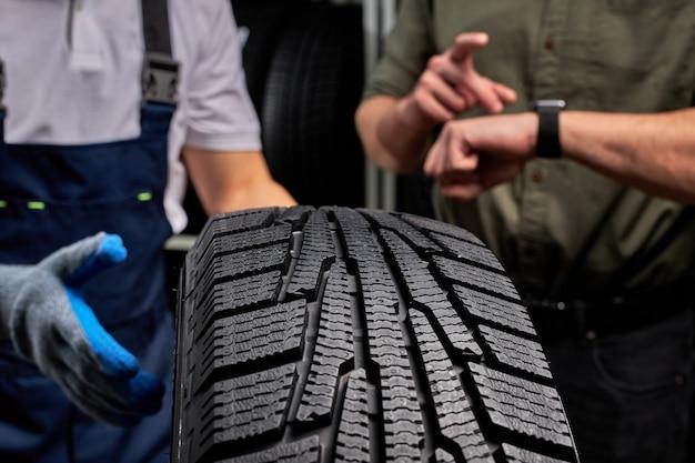 Foto ravvicinata del pneumatico per auto, focus sul pneumatico nero, cliente che esamina la superficie e le sue caratteristiche prima di effettuare l'acquisto