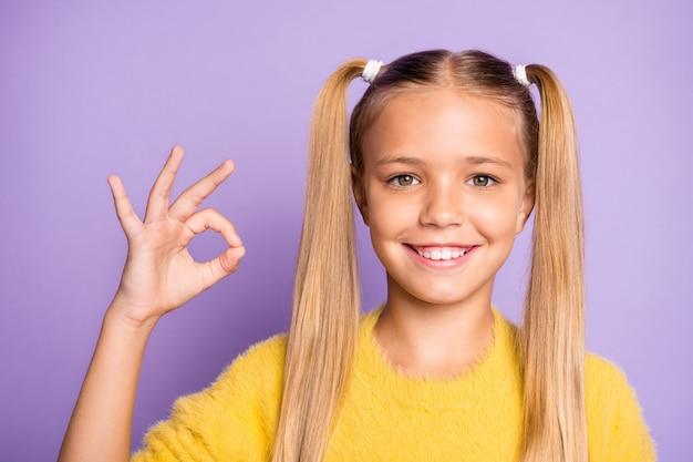 Chiuda sulla foto della ragazza raggiante dentata positiva casuale che mostra voi segno giusto che esprime emozioni positive sulla parete di colore pastello viola isolata del fronte