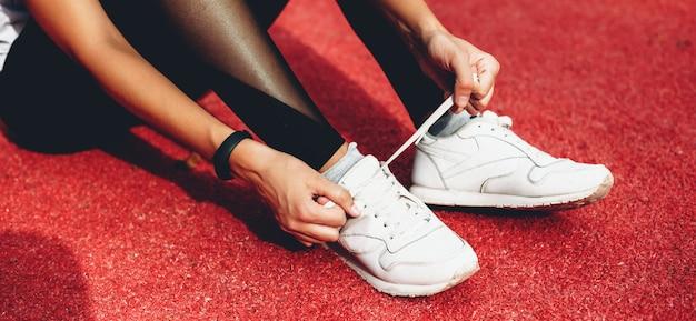 Primo piano foto di una ragazza caucasica che fissa le sue scarpe sportive prima di una croce su uno stadio rosso